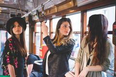 Three young women travelling on city tram - stock photo