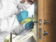 Forensic officer taking DNA swab off door handle Stock Photos