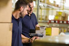 Male warehouse workers using barcode scanner in distribution warehouse - stock photo