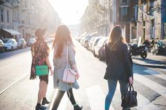 Rear view of three young women strolling over pedestrian crossing - stock photo