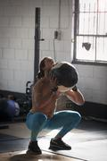 Crossfitter doing squats with medicine ball in gym Stock Photos