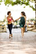 Young women walking on cobbled street - stock photo