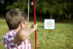 Rear view of teenage boy practicing archery Stock Photos