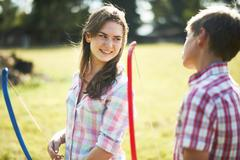 Teenage girl talking to brother whilst practicing archery - stock photo