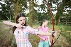Girl and teenage sister practicing archery Stock Photos