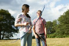 Teenage girl laughing with teenage brother whilst practicing archery Stock Photos