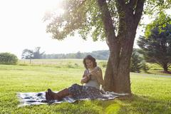 Woman on picnic blanket in field playing ukulele Kuvituskuvat