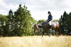Girl horseback riding in field - stock photo