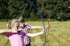 Girl and teenage brother practicing archery Stock Photos