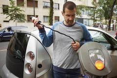 Man charging electric car on street, Paris, France - stock photo