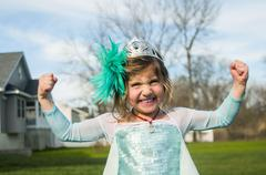 Girl in gown with feather fascinator playing outdoors - stock photo