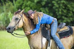 Portrait of mature woman, on horseback, hugging horse - stock photo