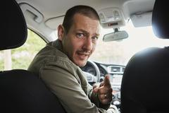 Mid adult man sitting in car, leaning over to back seat, pointing Stock Photos