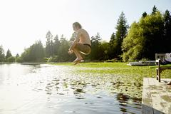 Man jumping into lake, Seattle, Washington, USA - stock photo