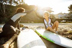 Couple sitting on beach, clapping hands in high five, surfboards beside them Stock Photos