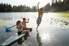 Couple paddling boat, man jumping into lake, Seattle, Washington, USA - stock photo
