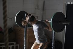 Crossfitter lifting barbell in gym - stock photo