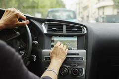 Woman sitting in car, using gps, focus on hands Kuvituskuvat