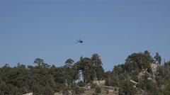 4K UHD blackhawk flies over trees mountain dissapears Stock Footage