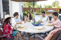 Young man and four adult sisters having family barbecue lunch on patio Stock Photos