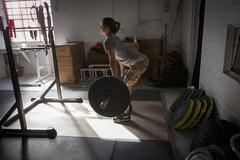 Crossfitter lifting barbell in gym Stock Photos
