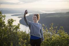 Woman taking selfie on hill, Angel's Rest, Columbia River Gorge, Oregon, USA Stock Photos