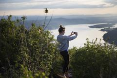 Woman taking photograph of view, Angel's Rest, Columbia River Gorge, Oregon, USA Stock Photos