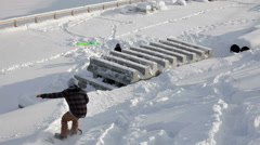 Snowboarder doing trick in the street on concrete blocks Stock Footage