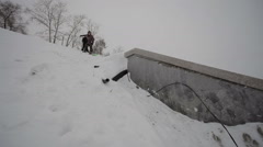 Snowboarder doing a slide trick in the street Stock Footage