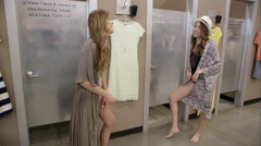 Teenage twin girls coming out of dressing room - stock footage