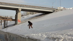 Snowboarder jumping over the street gap - stock footage