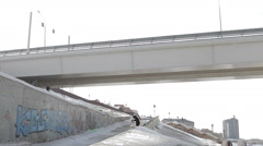 Skier jumping over the street gap on the bridge and sun background - stock footage