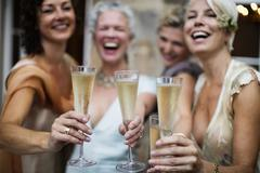 Elegant mature women toasting in urban garden Stock Photos