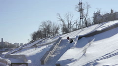 Skier doing a slide trick on a ledge in the street Stock Footage