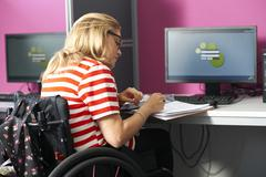 Teenage girl in wheelchair writing up file notes in class - stock photo