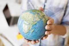 Cropped view of mature women hands holding small globe Stock Photos