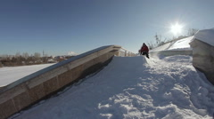 Skier doing a slide trick on a ledge in the street and falls Stock Footage