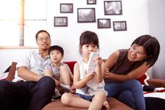 Young, modern Chinese family of parents and two young children sitting on sofa Kuvituskuvat