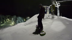 Snowboarder starts to move down the mountain at night Stock Footage
