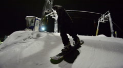 Snowboarder starts to move down the mountain and doing tricks at night Stock Footage