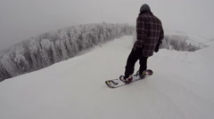 Snowboarder starts to move down the slope in snowpark Stock Footage