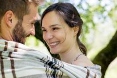 Head and shoulders of young couple wrapped in blanket face to face smiling Stock Photos