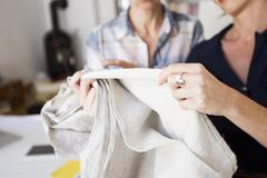 Cropped view of mature women holding and inspecting fabric - stock photo