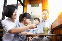 Young Chinese family having breakfast on the balcony in the sunshine together Stock Photos