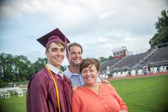 Young man standing with mother and father at graduation ceremony Stock Photos