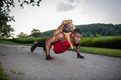 Young man doing pushups on rural road whilst giving dog a piggyback - stock photo