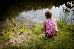 Rear view of girl crouching on riverbank looking water - stock photo