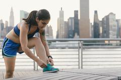Young woman in running clothes next to river tying her shoelace Stock Photos