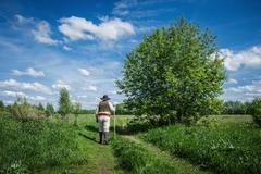 traveler in old clothes with a knapsack  on a country road - stock photo