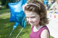 Portrait of young girl holding helium balloon, outdoors Stock Photos
